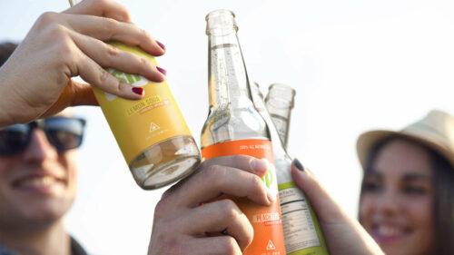 Sip branded bottles with people cheers or toasting