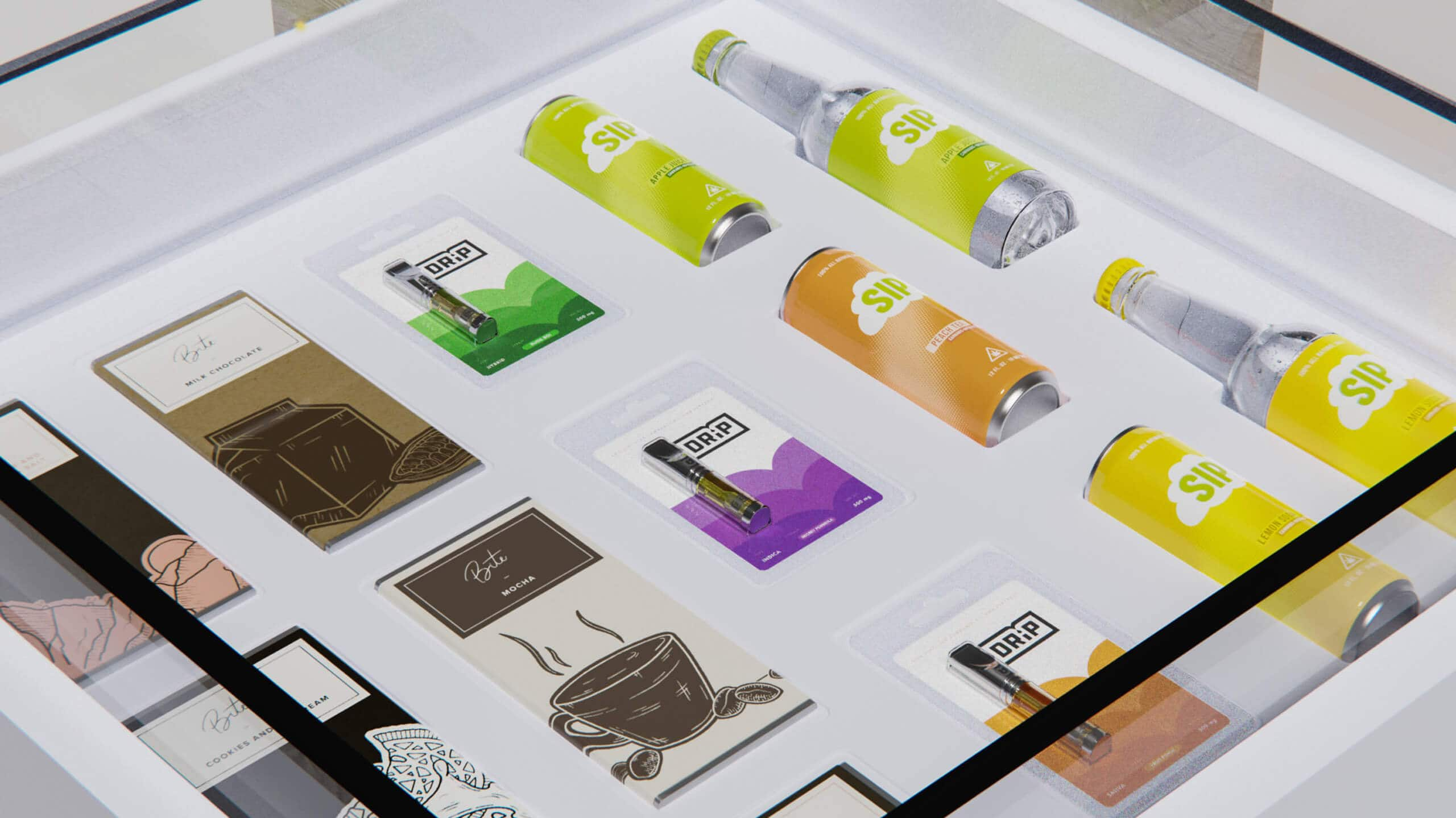 commcan bite sip drip cannabis packaging bottles cans cartridges in glass display
